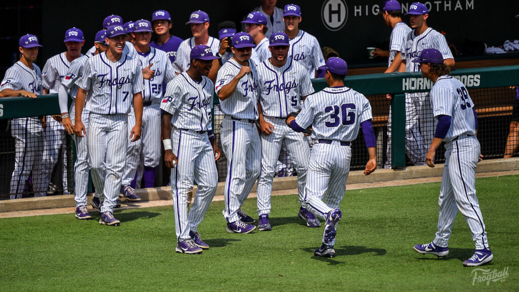tcu baseball players run out of the dugout to give each others fist bumps and congratulations