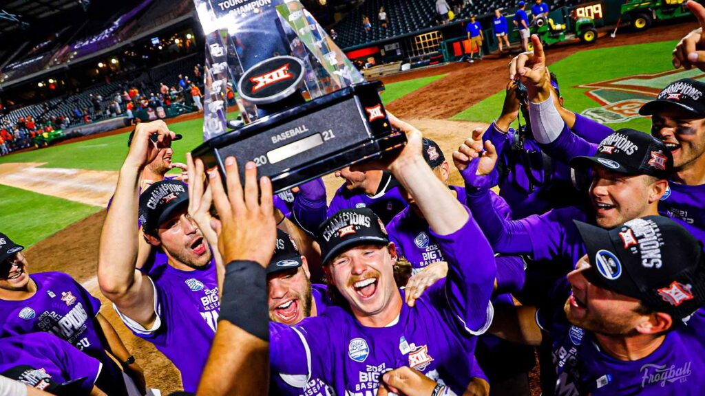 The tcu baseball team huddles together to celebrate the win of the Big 12 tournament with smiles and joy on their face while holding up the trophy