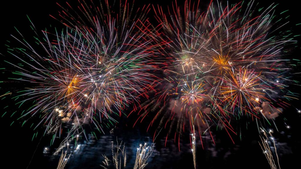 bright colors light up the dark sky as fireworks explode in the distance